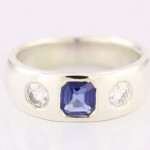 Blue Sapphire And Diamonds Flush Set In Platinum Ring, Blue Sapphire Em Cut With Two Round Brilliant Diamonds