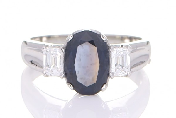 Blue Sapphire With Two Diamonds Placed On A Silver Ring