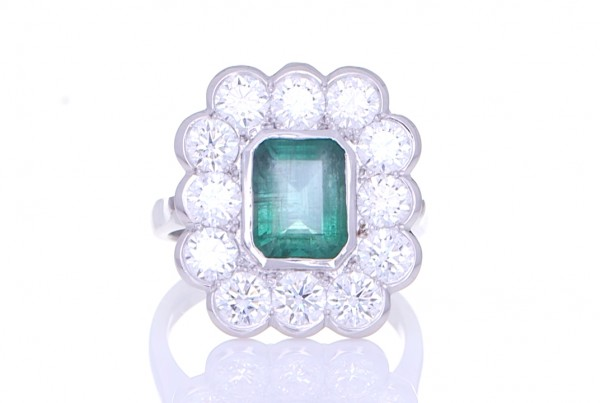Green Emerald Surrounded By Twelve Diamonds Placed On A Silver Ring