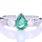 Green Emerald With Two Diamonds Placed On A Silver Ring