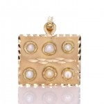 Six White Pearls Placed On A Golden Pendant