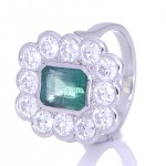 Twelve Diamonds Surrounding A Green Emerald Placed On A Silver Ring