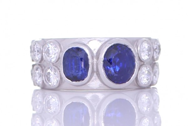Two Blue Sapphires With Twelve White Diamonds Placed On A Silver Ring