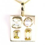 Two Golden Sapphires With A Yellow Emerald And A White Pearl Placed In A Golden Pendant
