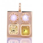 Two White Pearls With A Yellow and Golden Sapphire Placed On A Golden Pendant