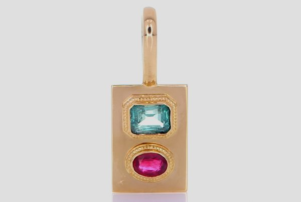 A Green Emerald With A Ruby Mounted On A Golden Pendant