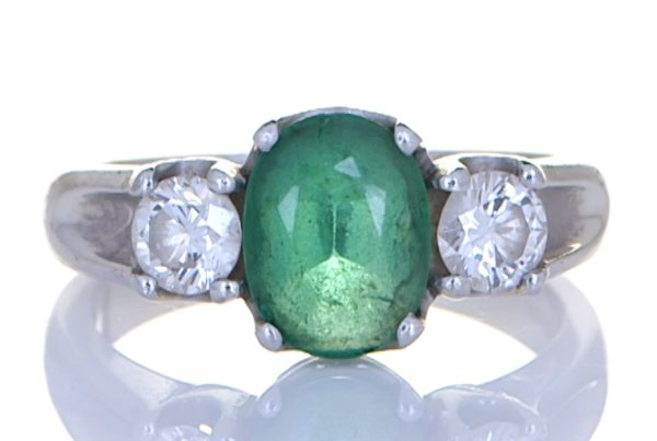 Green Emerald With Two Diamonds Mounted Onto A Platinum Ring