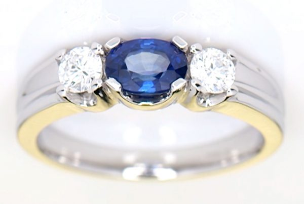 Two Diamonds With A Blue Sapphire Mounted Onto A Platinum Ring