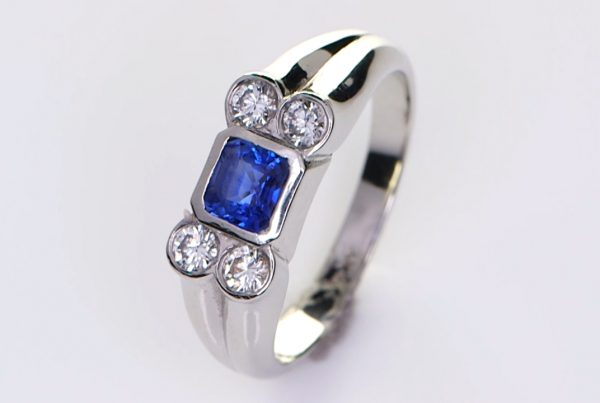 Four Diamonds With A Blue Sapphire Mounted On A Platinum Ring